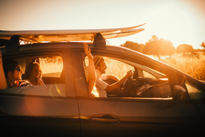 Friends in a car carrying a surfboard