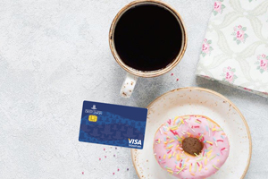 Visa Signature card next to coffee and donut
