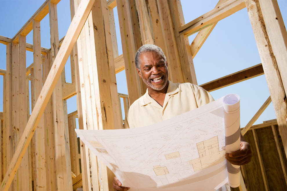 Image of an elderly man smiling and looking at building blueprints