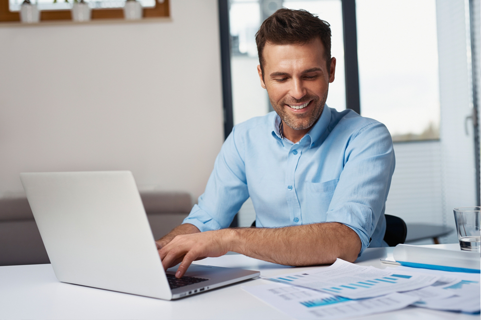 Image of a happy man on a laptop computer