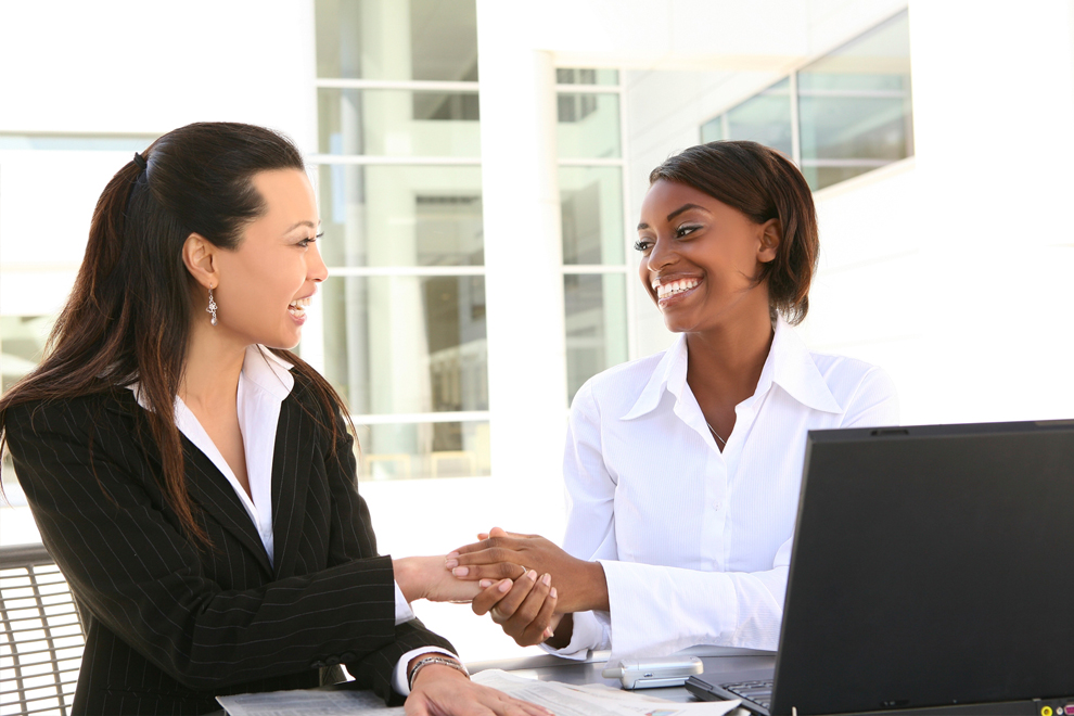 Image of two women in a business meeting shaking hands.